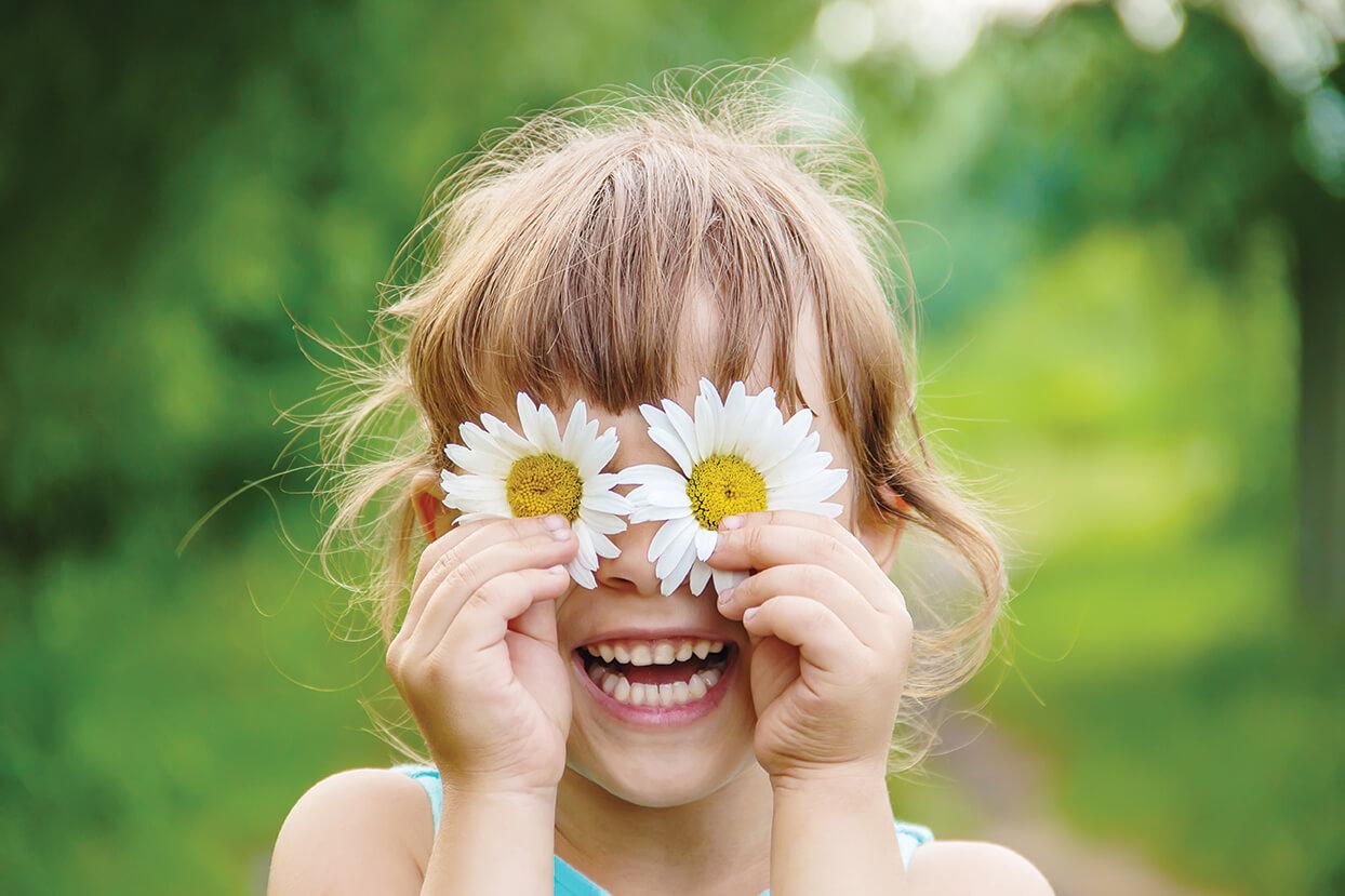 ילדה שמחה מחזיקה פרחים ליד העיניים